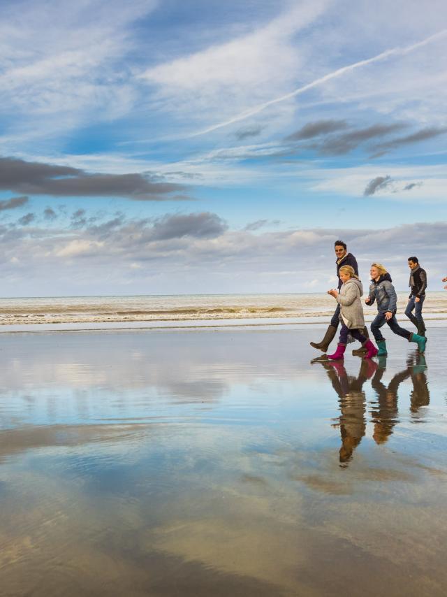 Famille en bottes et tenues hivernales marchant sur la plage à marée basse
