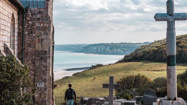 Jeune homme admirant le point de vue donnant sur la côte avec les falaises depuis le cimetière marin de l'église St Valery.