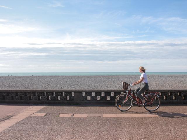 Jeune femme pédalant sur la piste cyclable du front de mer de Dieppe, galets et mer à l'horizon