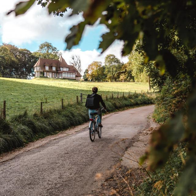 Jeune homme à vélo devant un manoir dans le village de Varengeville-Sur-Mer.