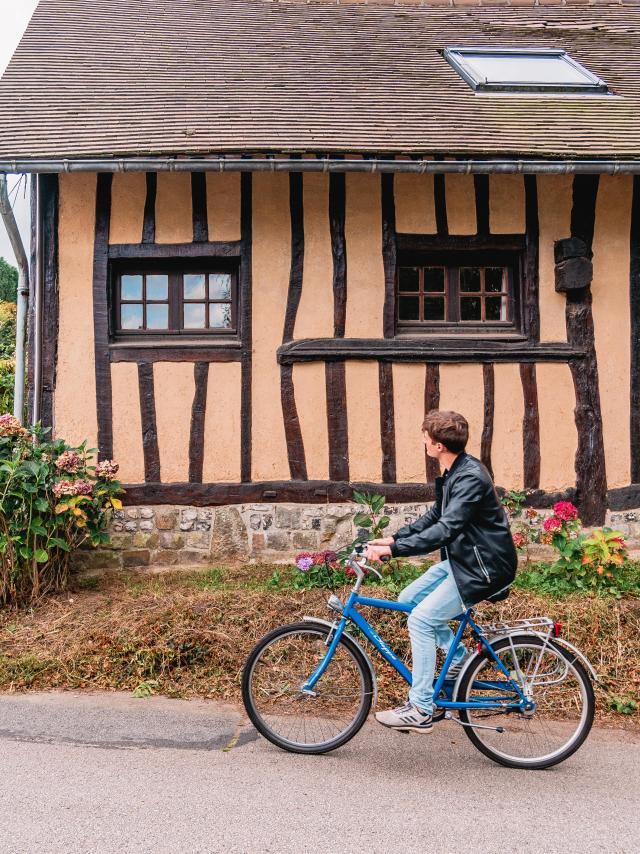Jeune homme à vélo devant une maison à colombage dans le village de Varengeville-Sur-Mer.