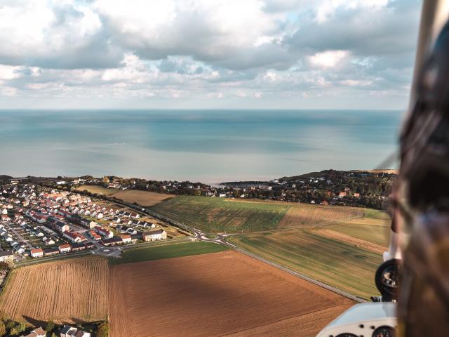 Vue du ciel sur la mer, sur la campagne et sur des habitations