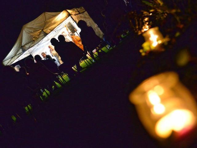 Personne écoutant un concert devant une tente, de nuit éclairé à la bougie