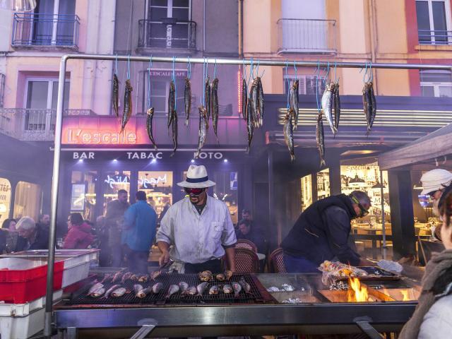 Homme faisant griller des harengs devant le bar l'Escale sur le quai Henri 4. Des harengs crus sont accrochés à une barre au-dessus du grill. A l'arrière-plan des personnes sont attablées en terrasse