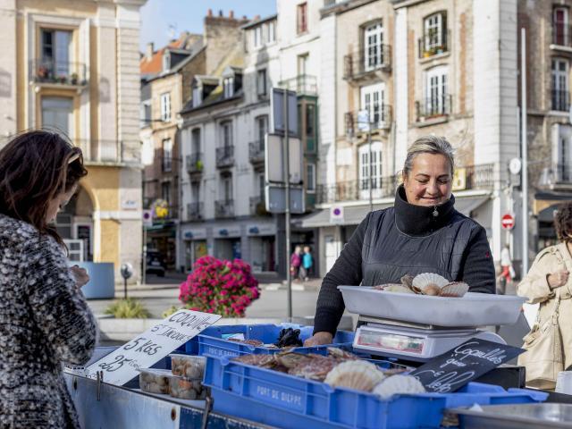 Une femme de pêcheurs vend des coquilles Saint-Jacques sur le marché aux poissons de Dieppe.