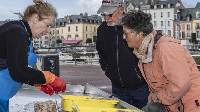 Une femme de pêcheur vend des coquilles Saint-Jacques sur le marché aux poissons de Dieppe.