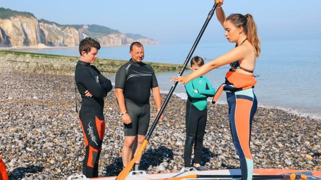 Une jeune femme sur une planche de paddle sur les galetsmontre le mouvement de la rame à un homme et 2 jeunes garçons en combinaison