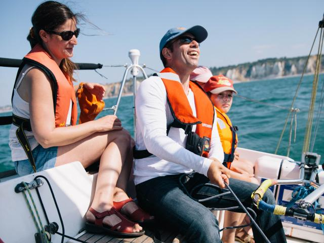 Un homme souriant tient la barre du voilier sous le regard d'une femme et d'un petit garçon