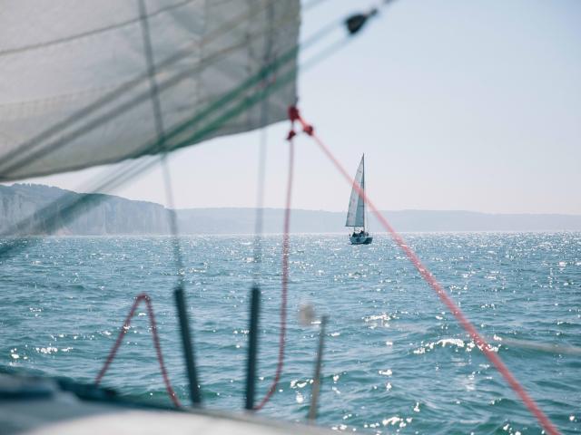 Depuis un voilier, vue sur un autre voilier au large et sur les falaises en arrière plan