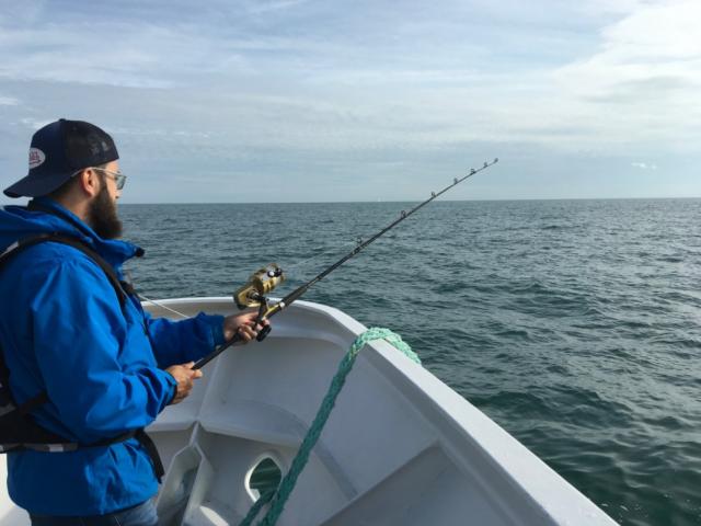 Jeune en homme pêchant avec une canne depuis un bateau