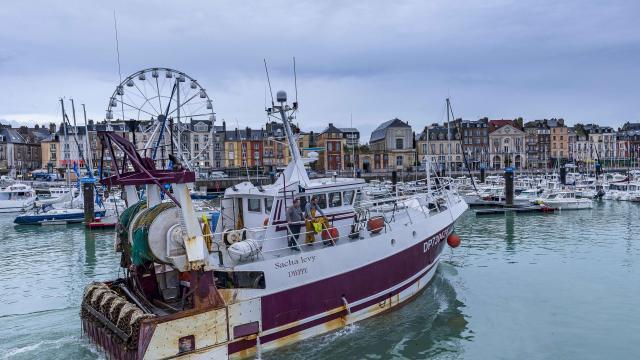 Bateau de pêche quittant le port, quai Henri IV et grande roue en arrière plan