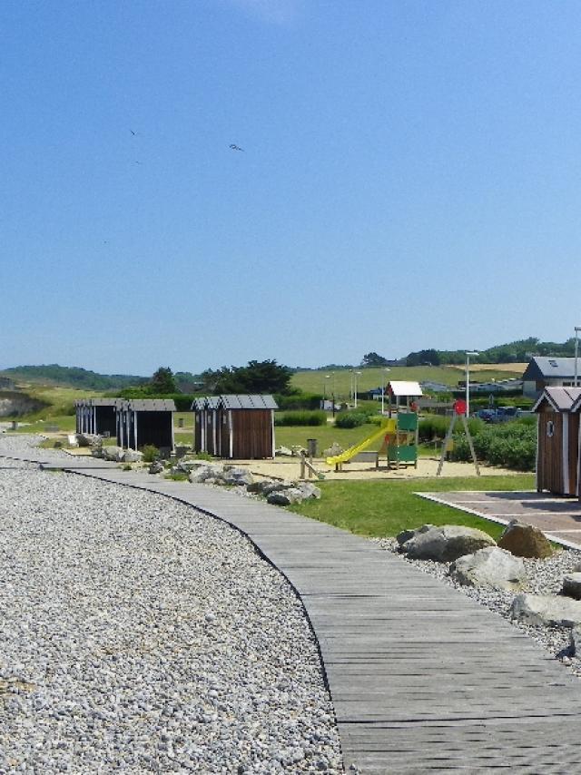 Cabines de plage en bois marron, aire de jeux et planches pour marcher sur les galets. Falaises et mer à l'arrière-plan