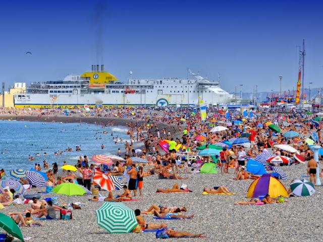 Plage de Dieppe en plein été. Nombreuses personnes installées sur les galets avec des parasols de toutes les couleurs. Le ferry entre dans le port en arrière-plan.