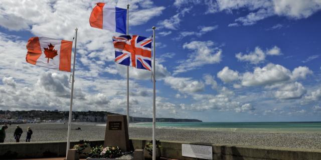 Drapeaux canadien, français et anglais flottant autour d'une stèle commémorative, plage et falaises en arrière-plan