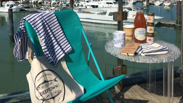 Produits de la boutique de l'Office de Tourisme (marinière, tote bag Deeptown, cidre, miel, caramels de pommes, mug, carnet, stylo) présentés sur un transat et une table avec le port de plaisance en arrière-plan.