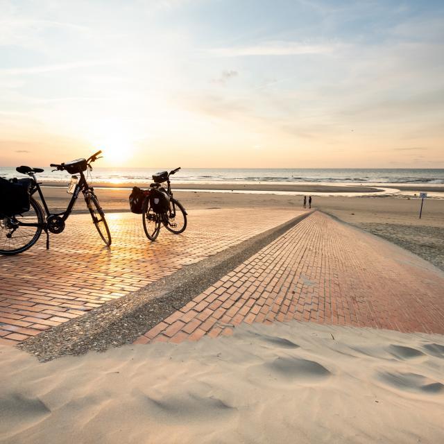 Vélos sur la dige de Leffrinckoucke au soleil couchant.