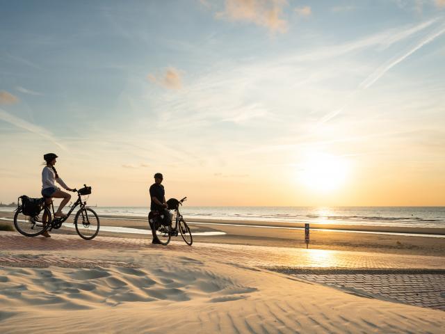 Cyclistes regardant le coucher de soleil sur la plage de Leffrinckoucke