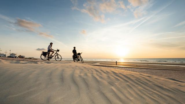 Cyclistes regardant le coucher de soleil sur la plage de Leffrinckoucke.