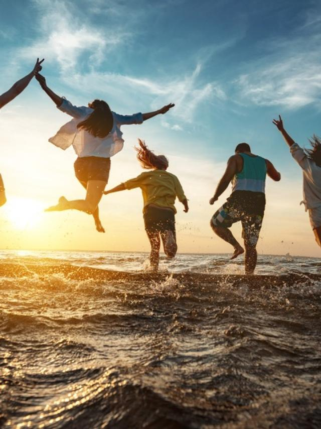 Five happy friends runs and jumps to sunset lake beach after party