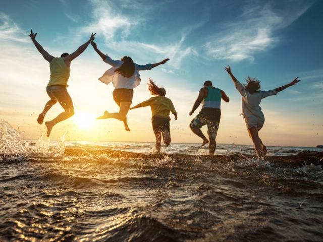 Five happy friends run and jump to sunset lake beach after party