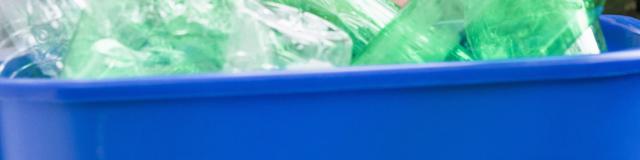 Woman hiding behind recycling bin