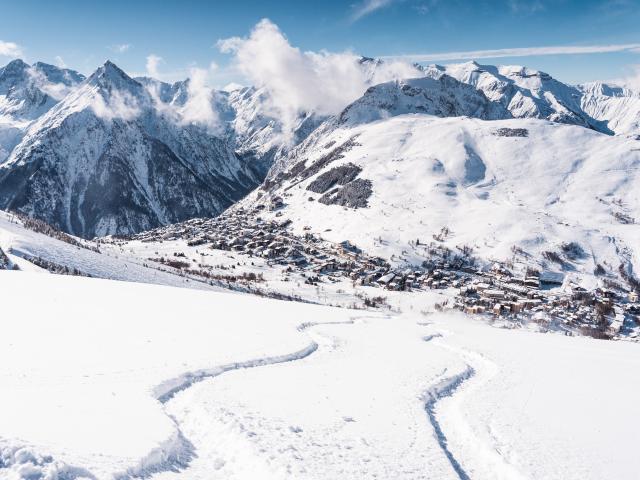 Panorama sur la station des 2 Alpes avec deux traces de ski dans la neige poudreuse au premier plan