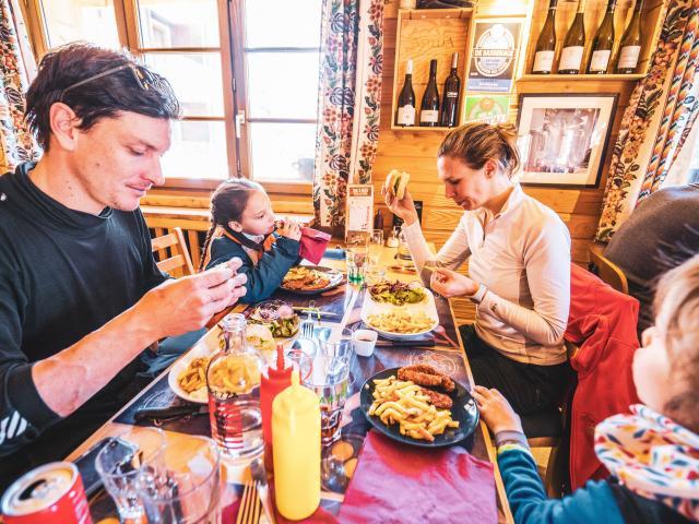 Une famille qui déjeune dans un restaurant de la station des 2 Alpes après une sortie ski