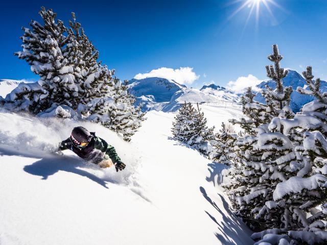Virage en snowboard un jour de ciel bleu et de neige fraîche aux Deux-Alpes