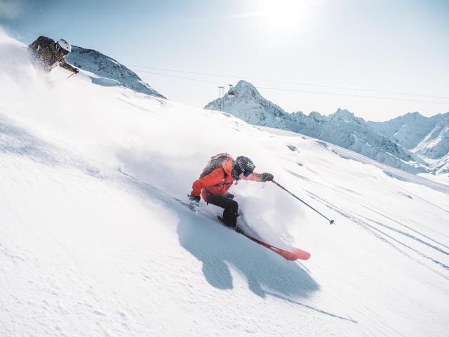 Virage poudreuse sous les remontées mécaniques aux Deux-Alpes en ski