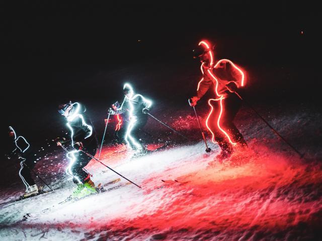 Démonstration de ski de nuit par les moniteurs lors des vacances de fin d'année dans la station des Deux-Alpes