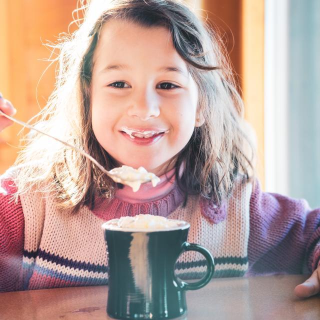 Jeune fille profitant de son chocolat chaud dans un restaurant de altitude de la station de ski Les Deux Alpes