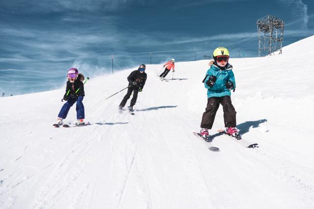 Ski est en famille avec les enfants devant les parents au Deux-Alpes