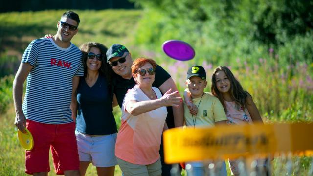 famille jouant au Disc-Golf aux 7 Laux en été