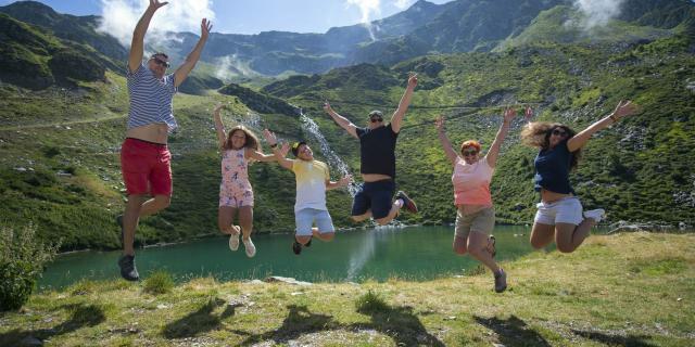 famille sautant de joie aux 7 Laux en été devant un lac