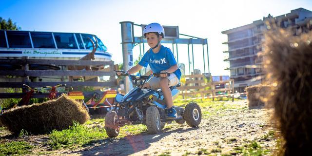 Enfant en quad éléctrique aux 7 Laux en été à Prapoutel