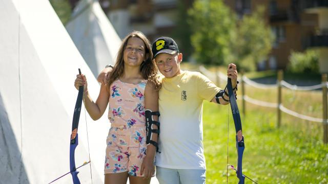 Deux enfants en train de faire du tir à l'arc aux 7 Laux en été