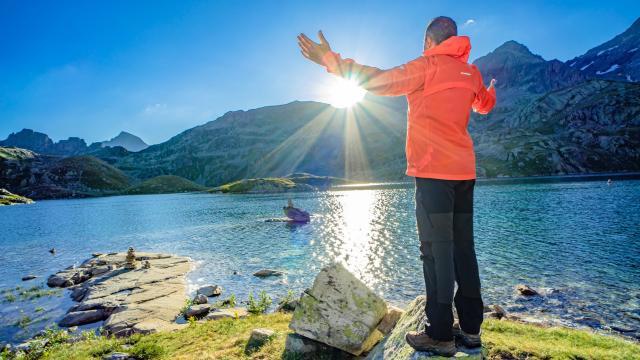 Randonneur devant un lac aux 7 Laux en été