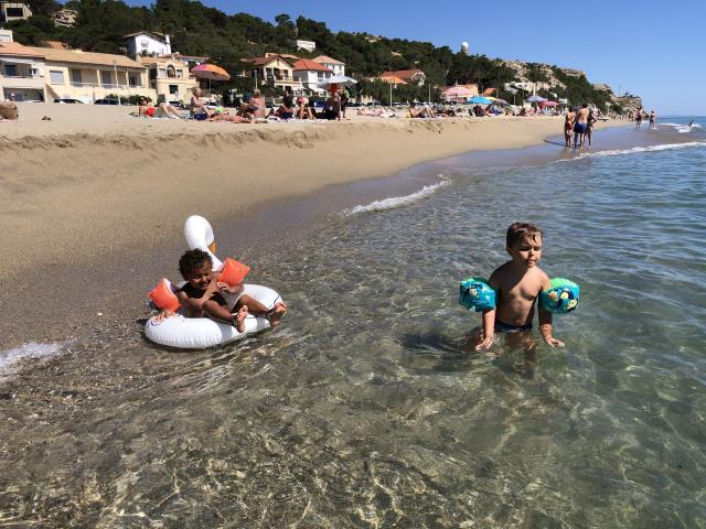 Photo d'enfants avec brassards et bouée sur la plage de Leucate Plage