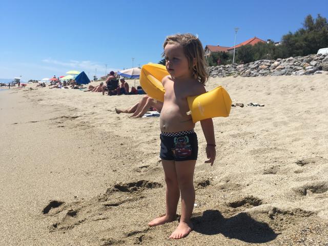 Photo d'un enfant avec ses brassards sur la plage de Leucate Plage