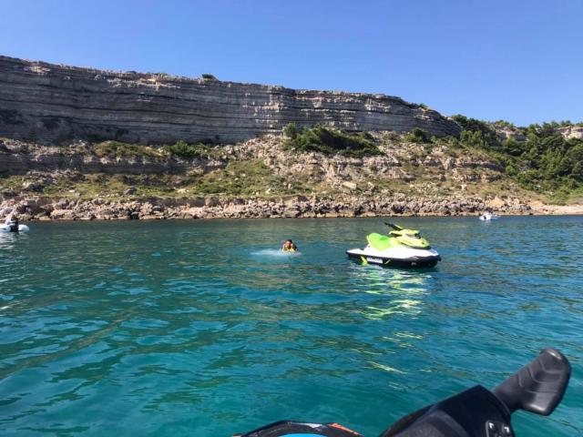 Photo de jet ski au large de Leucate, en fond la falaise et des personnes qui se baignent