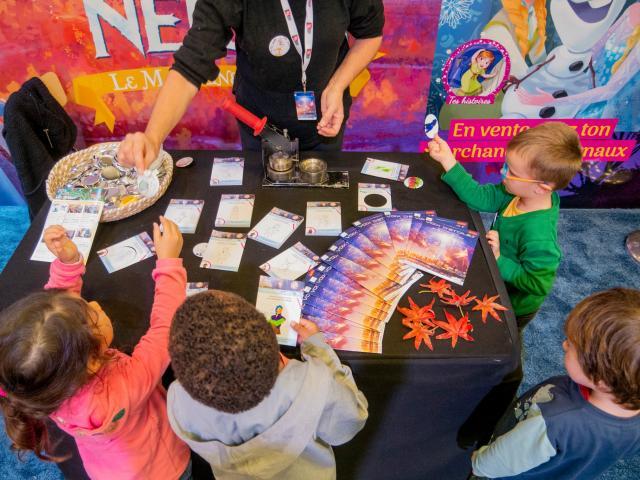 Photo d'enfants jouant avec des cartes et magazines sur une table pendant le festival Voix d'Etoiles à Port Leucate
