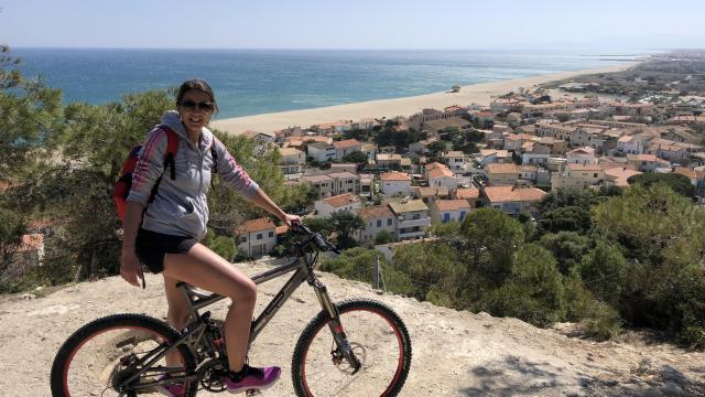 Photo d'une jeune fille sur son vélo avec en 2ème plan la plage et Leucate Plage vu d'en haut de la falaise