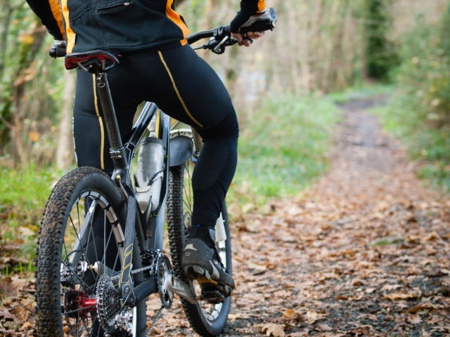 Cyclist standing in front of a path of the forest with a copy space on your right