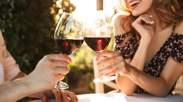 Cropped image of young loving couple sitting in cafe by dating outdors in park holding glasses of wine drinking.