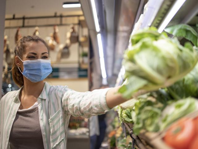 Woman with hygienic mask and rubber gloves and shopping cart in grocery buying vegetables during corona virus and preparing for a pandemic quarantine.