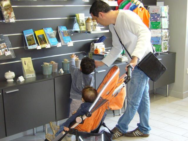 Un père et ses enfants regardant la boutique de l'Office de Tourisme