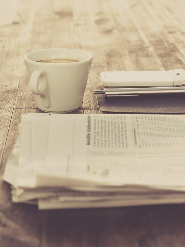 Journal et tasse à café sur une table