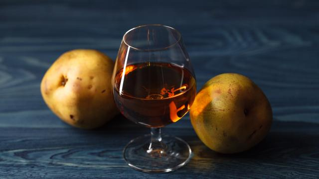 traditional fruit brandy and pears on a vintage grunge wooden background
