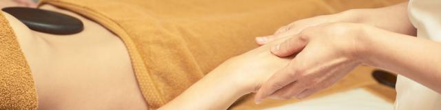 body arm stone massage. Hot rock masseur. Girl at salon with doctor hands. Relax spa resort.