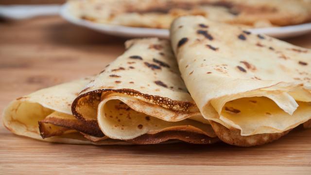 crêpes dans une assiette sur fond de planche à découper en bambou